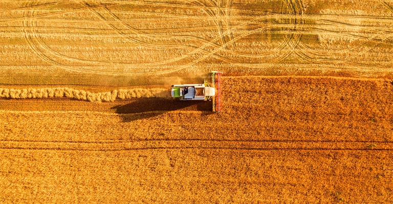 Harvester machine working in field, LALS Stock | Shutterstock